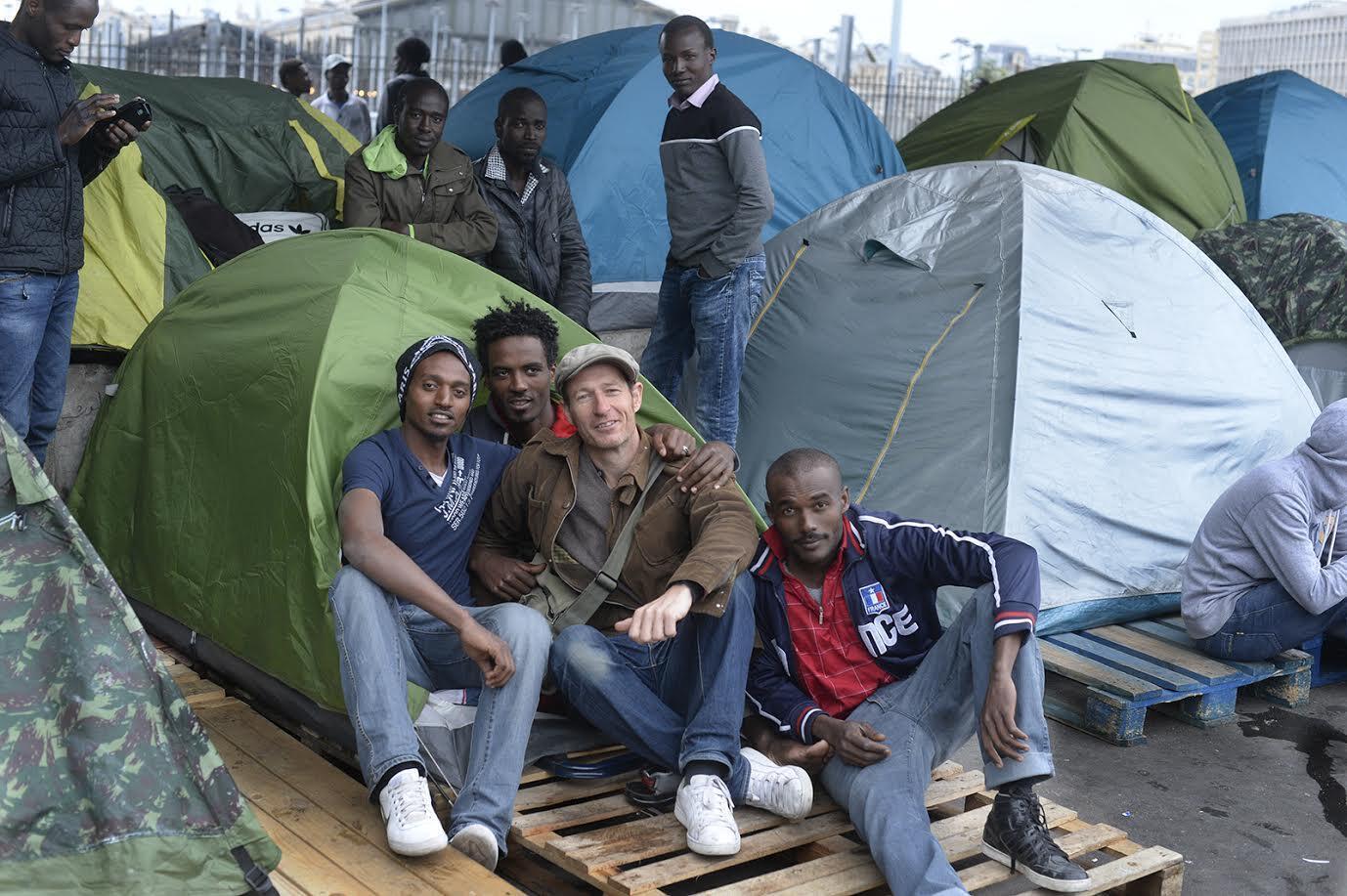 Le photographe Jean-Baptiste Pellerin avec des migrants au métro La Chapelle, Paris.