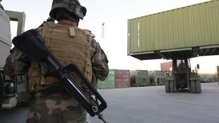 A French soldiers checks the loading of containers, ready to be sent to France, as part of the withdrawal of the French troops at Warehouse French base in Kabul, November 19, 2012
