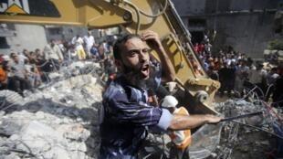 Policía palestino delante de una casa que fue destruida durante el bombardeo israelí que mató a tres jefes militares del Hamas en Rafah, Franja de Gaza, 21 de agosto de 2014.