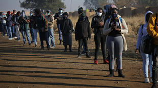Commuters in South Africa wearing face masks wait outside the Pienaarspoort Station, East of Pretoria to board a train
