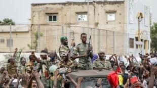 Des membres des forces armées du Mali sont acclamés par la foule suite à l'arrestation du président IBK et du Premier ministre Boubou Cissé, le 18 août 2020.