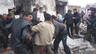 Les combattants de l'Armée syrienne libre (ASL) et les habitants de Halfaya, le 23 décembre 2012, sur les lieux du bombardement.