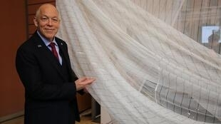 CEO Michael Anderson stands in front of the new mosquito net
