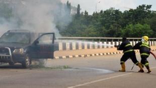Des pompiers éteignent un véhicule en flammes à la suite d'affrontements entre les forces de l'ordre et des manifestants du Mouvement islamique du Nigeria, devant les locaux de l'Assemblée nationale à Abuja, le 9 juillet 2019