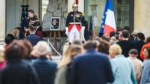 People wait to sign a condolence registers for late former French President Jacques Chirac at the Elysee presidential palace in Paris.