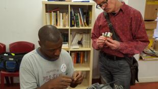 Edisson et Vincent, au Repair café, tentent de bricoler un aspirateur qui semblent ne plus fonctionner.