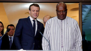 French President Emmanuel Macron (L) is met at Ouagadougou airport by Burkoina Faso's Roch Marc Christian Kaboré.