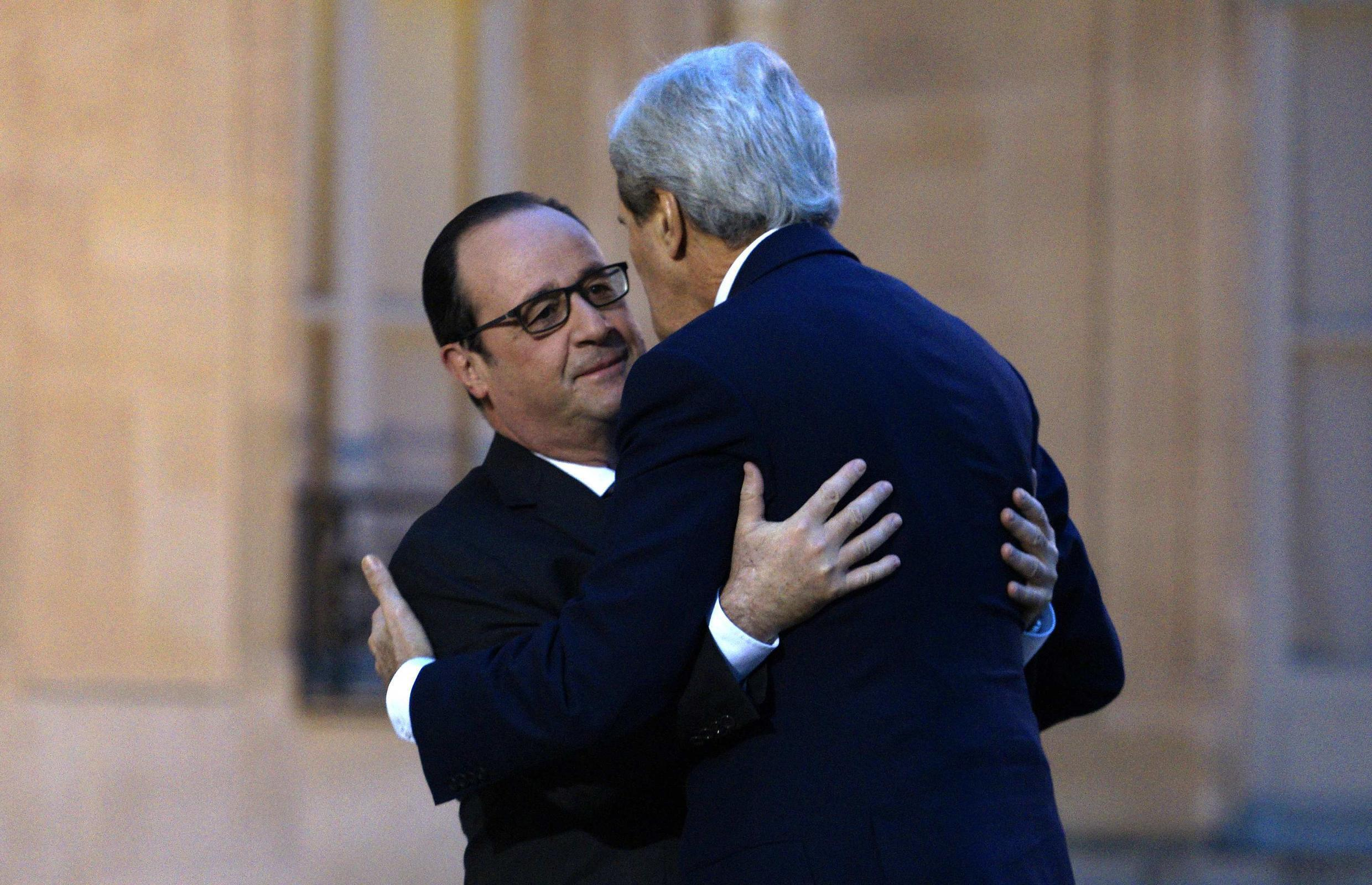 French President Francois Hollande embraces U.S. Secretary of State John Kerry upon Kerry's arrival at Elysee Palace in Paris, 16 January 2015.