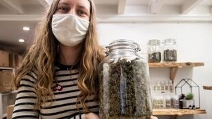 """No high here: A saleswoman with a jar of CBD marijuana buds at """"Le Chanvrier Francais"""" in Paris."""
