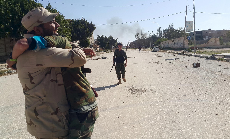 Des soldats loyaux au gouvernement libyen reconnu célèbrent la reprise d'un des principaux bastions des jihadistes à Benghazi, le 23 février 2016.