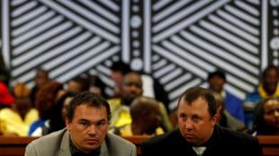 Sentados no banco do tribunal de Delmas, na África do Sul, os fazendeiros Willem Oosthuizen e Theo Martins, acusados de terem tentado prender um homem negro vivo dentro de um caixão, em 31 de julho de 2017.
