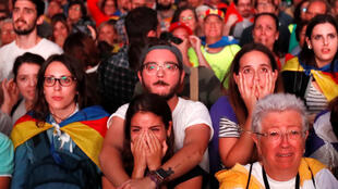 People react as they watch a sesion of the Catalonian regional parliament on a giant screen at a pro-independence rally in Barcelona, Spain, October 10, 2017.