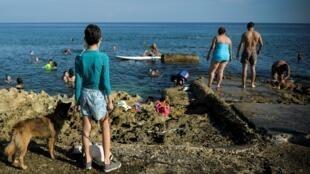 Les gens profitent du front de mer du Malecon à La Havane le 3 juillet 2020, alors que la capitale cubaine entre dans la première phase de déconfinement.