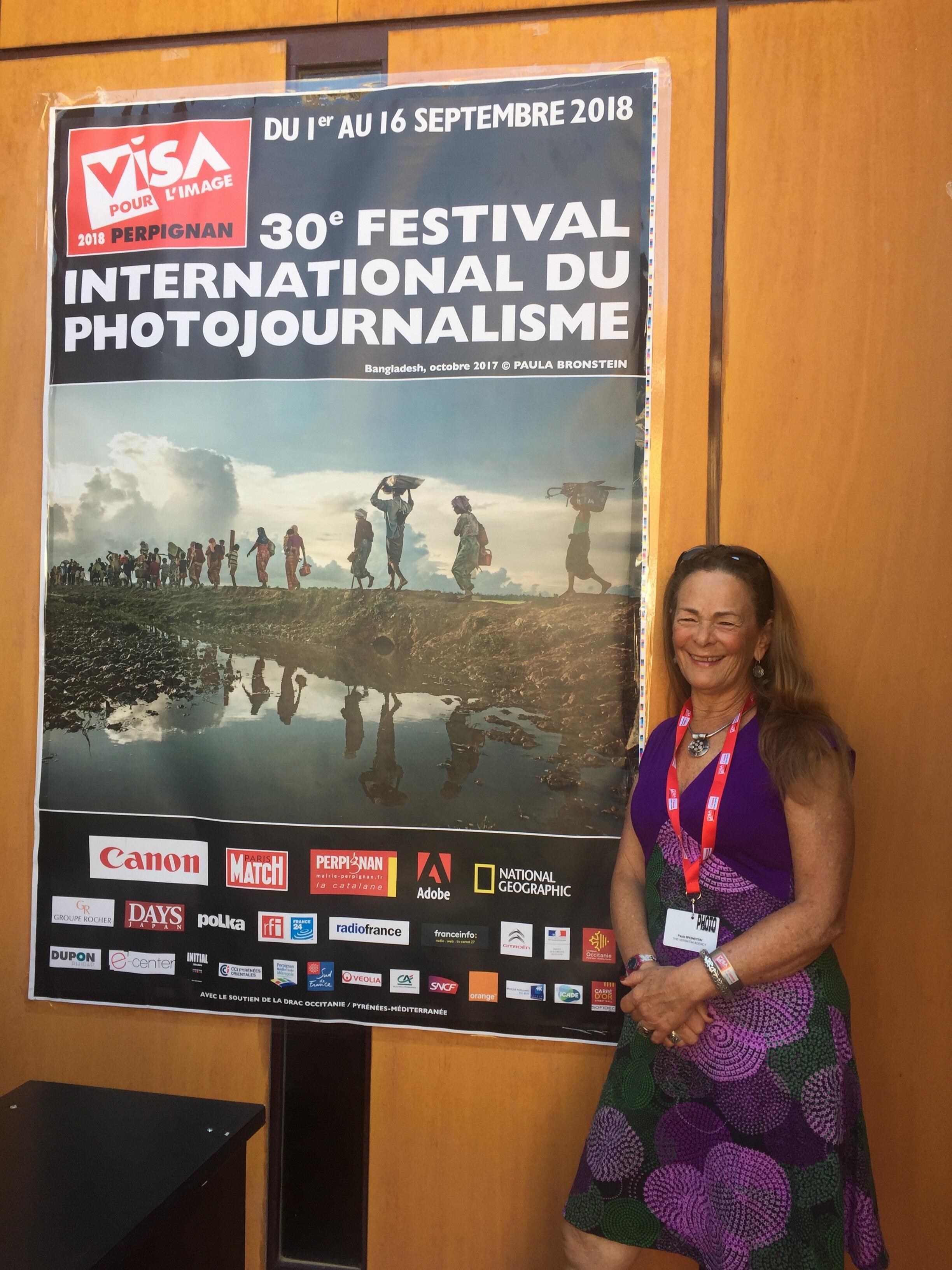 Paula Bronstein diante do cartaz do festival Visa pour L'Image com foto sua sobre a minoria rohingya.