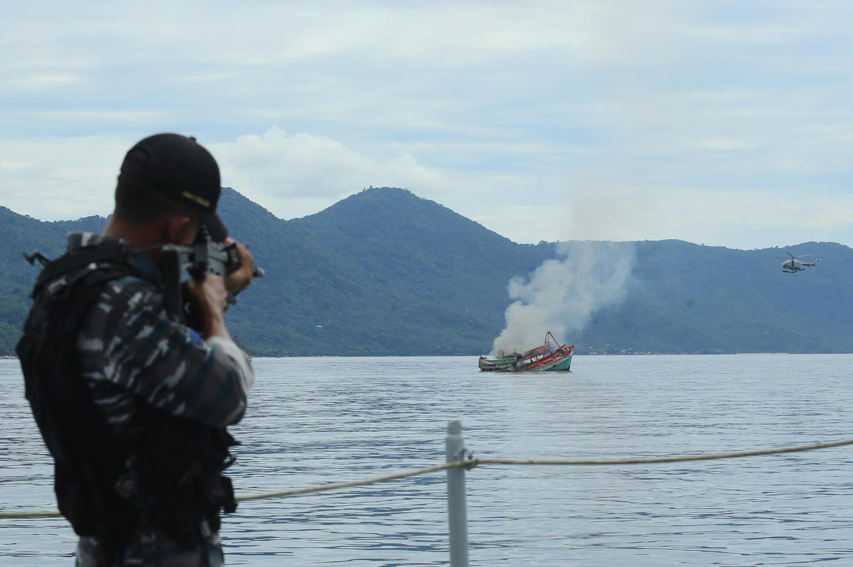 Một sĩ quan hải quân Indonesia đang bắn hủy một tàu cá Việt nam bị bắt giữ trong vùng biển thuộc đảo Anambas, tỉnh Riau  ngày 5/12/2014.