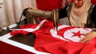 Une femme coût le drapeau national tunisien dans une boutique, à Tunis. (Photo d'illustration)