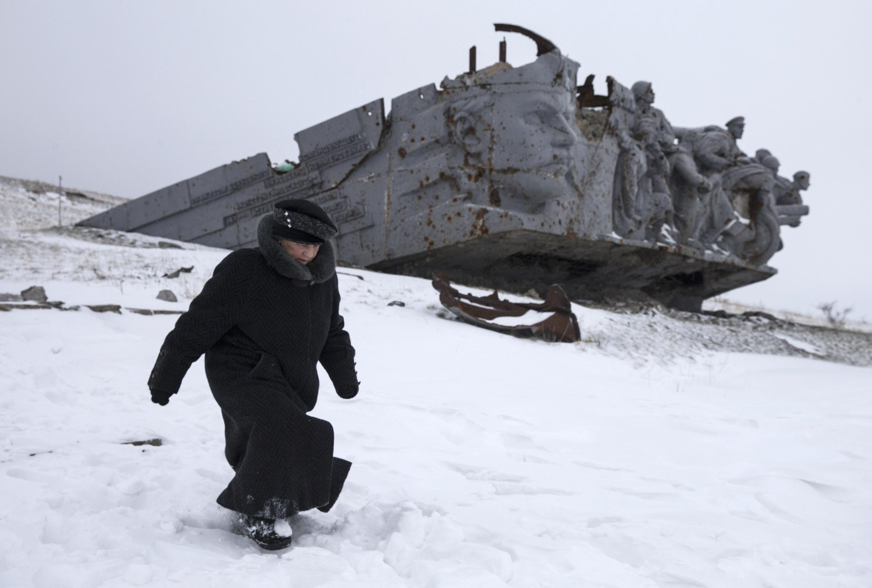 Mulher caminha ao lado de um memorial de guerra destruído em Savur-Mohyla, a leste de Donetsk.