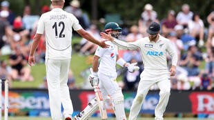 New Zealand's paceman Kyle Jamieson (L) gets a high five from captain Kane Williamson (R) at the lunch break on day one of the second cricket Test match between New Zealand and Pakistan at Hagley Oval in Christchurch