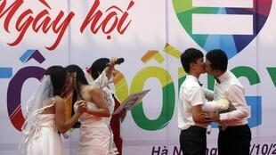 Same-sex couples Le Thuy Linh (L) and Tran Ngoc Diem Hang (2nd L), and Ho Hai Thinh (2nd R) and Pham Tien Dung (R), kiss during their public wedding as part of a lesbian, gay, bisexual, and transgender (LGBT) event on a street in Hanoi October 27, 2013.