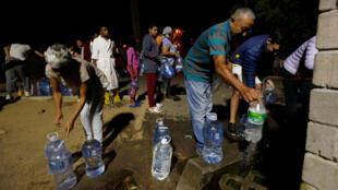 Sul-africanos enchem garrafas de água na Cidade do Cabo, que enfrenta racionamento.