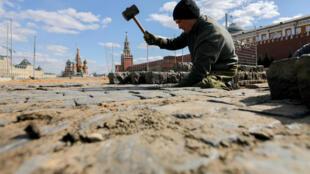 Рабочий укладывает брусчатку на Красной площади в Москве. 28 апреля 2020 г.