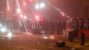Des policiers libanais essuient des tirs de feux d'artifice devant le Parlement à Beyrouth le 18 janvier 2020.