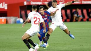 La star du FC Barcelone Lionel Messi est cernée par les joueurs du Séville FC Sergio Reguilon et Diego Carlos, lors du match nul le 19 juin 2020, en Andalousie