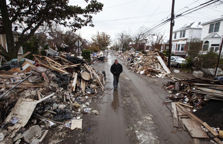 Un homme longe une pile de débris laissés par l'ouragan Sandy, le 8 novembre 2012, dans le quartier de Belle Harbor, dans le Queens.