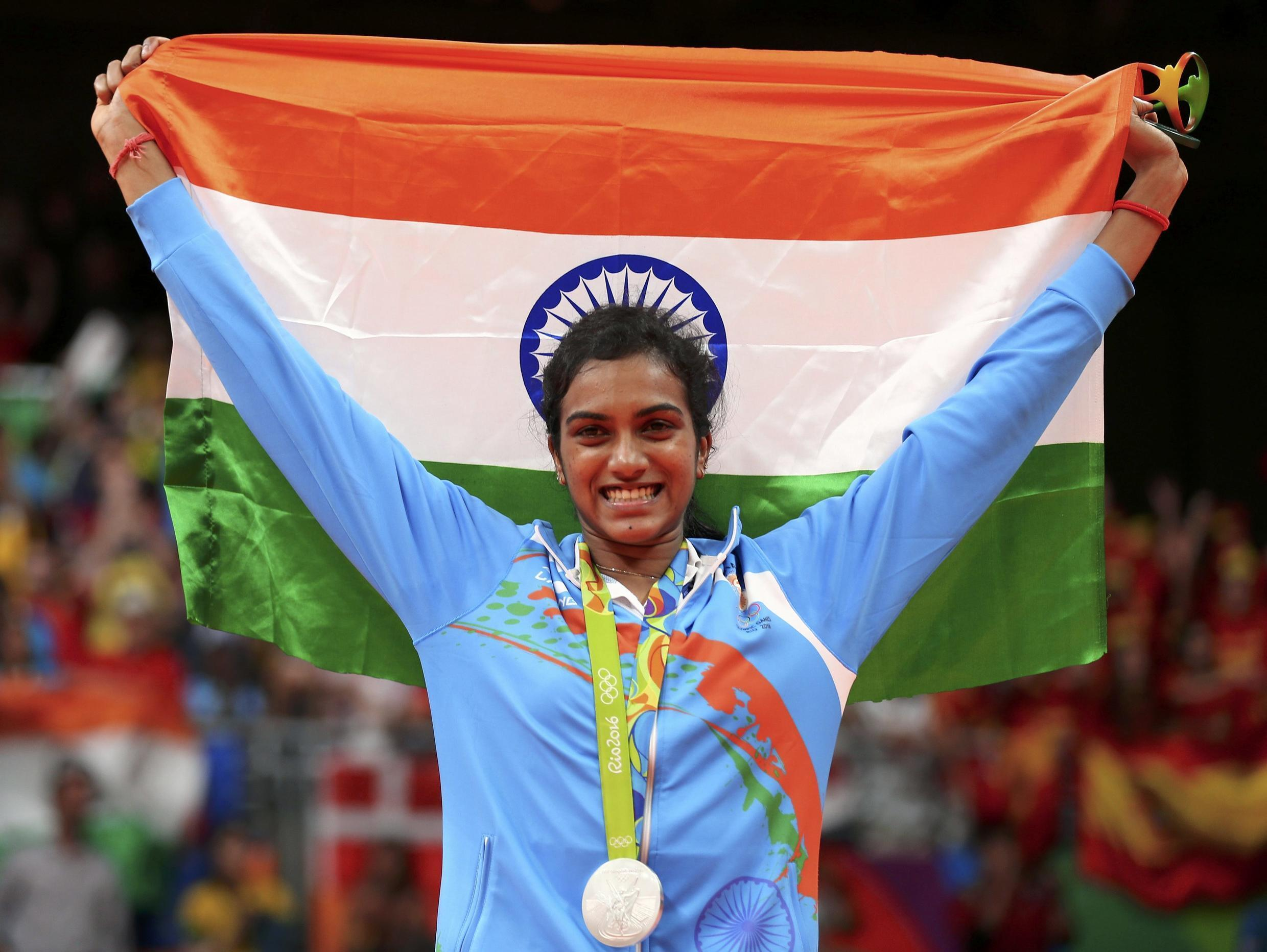 India's P.V. Sindhu holds up her country's flag while posing with the silver medal.