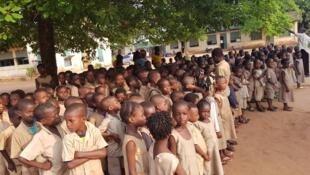 Dans la cour de récréation, les enfants patientent en rang.