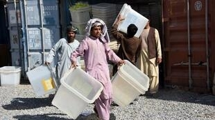 Empleados de la Comisión electoral descargan urnas para la vaotación en la provincia de  d de Kandahar, 26 octubre 2018.