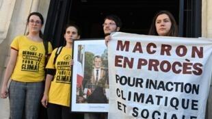 Les activistes posent devant la mairie de Saint-Ouen avec un portrait du président français retiré de la mairie de Saint-Ouen, près de Paris. , le 11 septembre 2019.