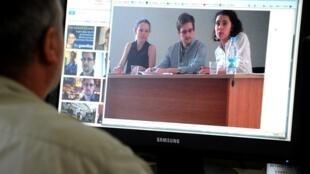 Sur l'écran, Edward Snowden lors de sa rencontre avec des activistes à l'aéroport de Moscou.