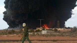 A rebel walks past a burning oilfield in Libya
