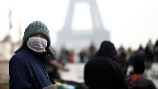 Un homme porte un masque facial sur l'esplanade du Trocadéro en face de la Tour Eiffel à Paris, le 25 janvier 2020.