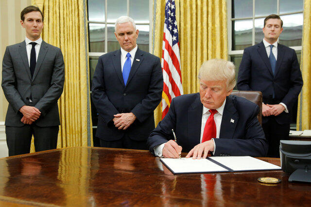 U.S. President Donald Trump, flanked by Senior Advisor Jared Kushner (standing, L-R), Vice President Mike Pence and Staff Secretary Rob Porter welcomes reporters into the Oval Office for him to sign his first executive orders at the White House in Washingt