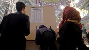 Des Iraniens devant les listes de candidats dans un bureau de vote à Téhéran, ce vendredi 26 février 2016.