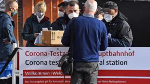 Um viajante fica em frente a um centro de testes de coronavírus na estação central em Colônia, Alemanha, domingo, 11 de outubro de 2020. A 4ª maior cidade da Alemanha informou ter ultrapassado o importante nível de alerta de 50 novas infecções por 100.000 habitantes em sete dias.