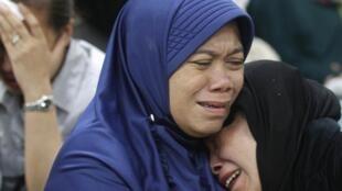Familiares dos passageiros do superjato Sukhoi, que explodiu na Indonésia nesta quarta-feira, choram seus mortos no aeroporto de Jacarta.