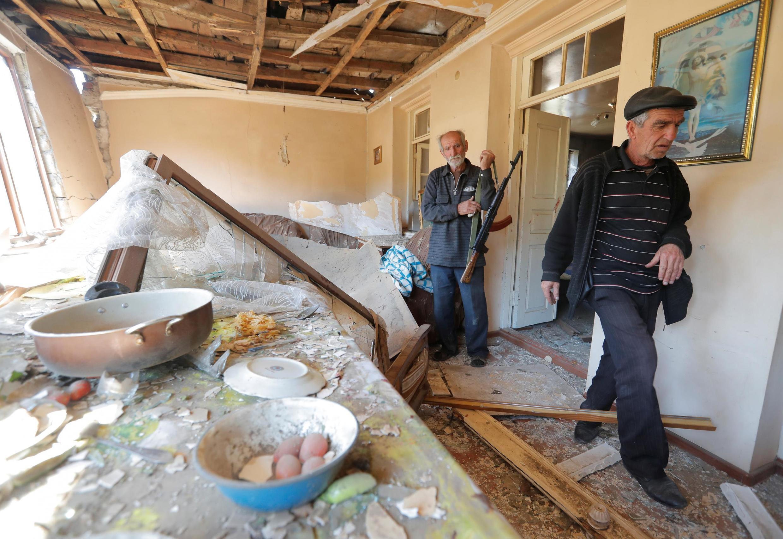 Des résidents de la ville de Shosh montrent les dégâts sur une maison dus aux combats dans la région du Haut-Karabakh, le 17 octobre 2020.