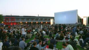 Des spectateurs sont installés sur une pelouse pour assister à une projection en plein air dans le parc de la Villette à Paris.