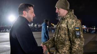 Le président Volodymyr Zelenskiy salue une prisonnier libéré lors de son arrivée à Kiev, le 29 décembre 2019.