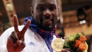 O judoca francês, Teddy Riner, exibe sua medalha de ouro, el L