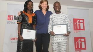 Cécile Mégie, directrice de RFI, entoure les lauréats, Cécile Goudou (g) et Didier Guedou, à Cotonou, le 2 novembre 2016.