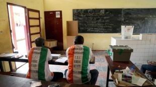 Des assesseurs attendent les électeurs dans un bureau de Yougon, à Abidjan, le 31 octobre 2020.