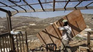 Un colono judío construyendo una casa en Cisjordania.