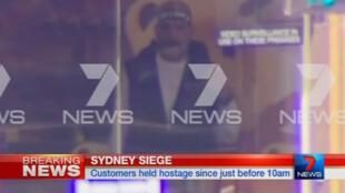 O canal de televisão local 7 News exibe imagem do sequestrador através da janela do Lindt Chocolate Cafe, em Sidney.