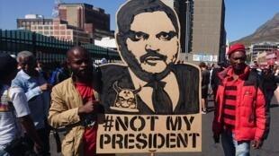 Waandamanaji wakibebelea picha ya mmoja wa ndugu wa familia ya Gupta Cape Town, Aprili 7, 2017