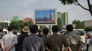 North Koreans watch the missile launch on a giant screen in Pyongyang