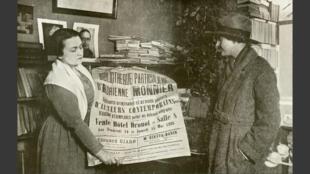 Adrienne Monnier, à gauche, en 1926, avec une affiche publicitaire de la Maison des Amis des Livres, sa librairie.